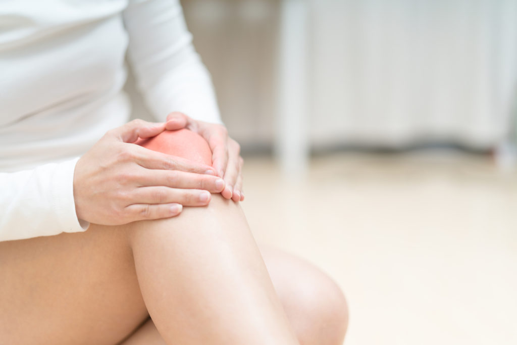 Swollen knee pain injury women sitting and touch her knee painful, healthcare and medicine concept