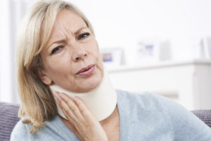 Mature Woman Suffering from Whiplash Wearing Surgical Collar In Pain