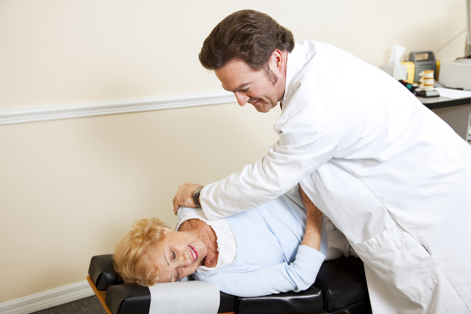 Chiropractor adjusting a female patient's spine.  Plenty of room for text.