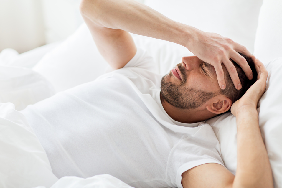 people, bedtime and rest concept - man lying in bed at home suffering from headache