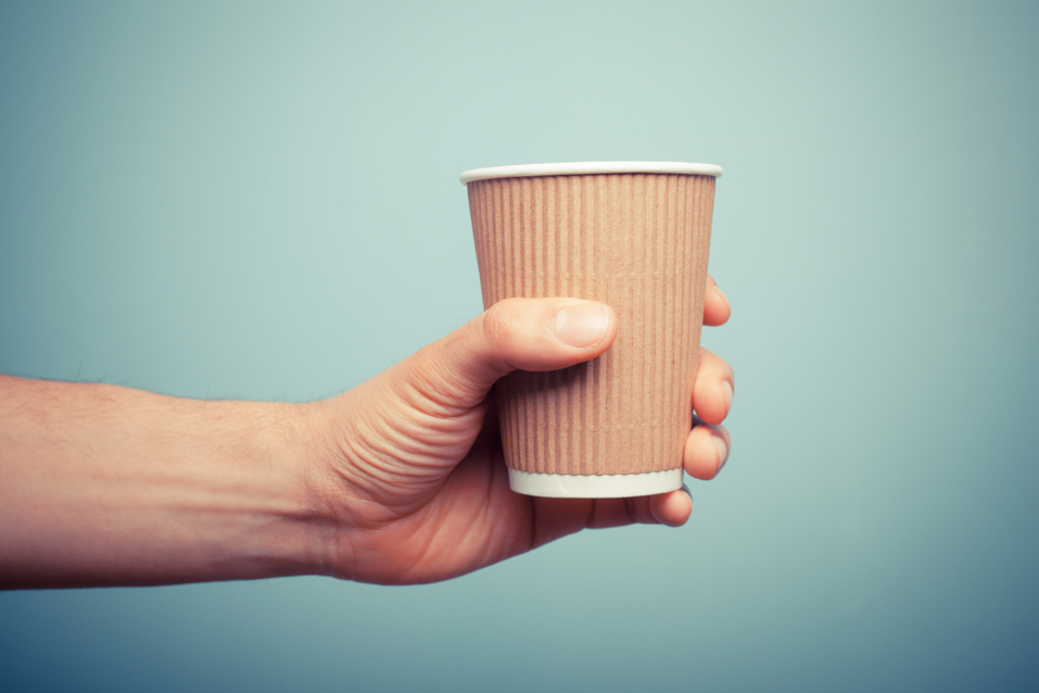 A man is holding a coffee Cup