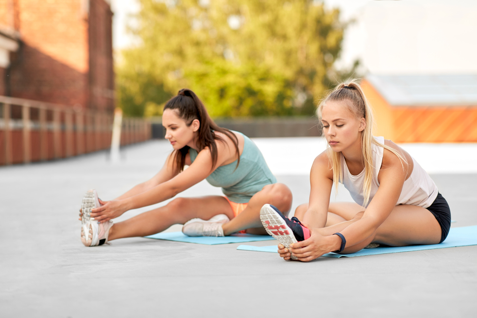 fitness, sport and healthy lifestyle concept - young women or female friends with activity trackers stretching outdoors