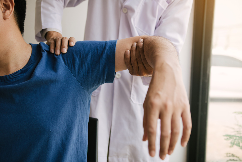 Physical therapists press to the patient shoulder check for pain.