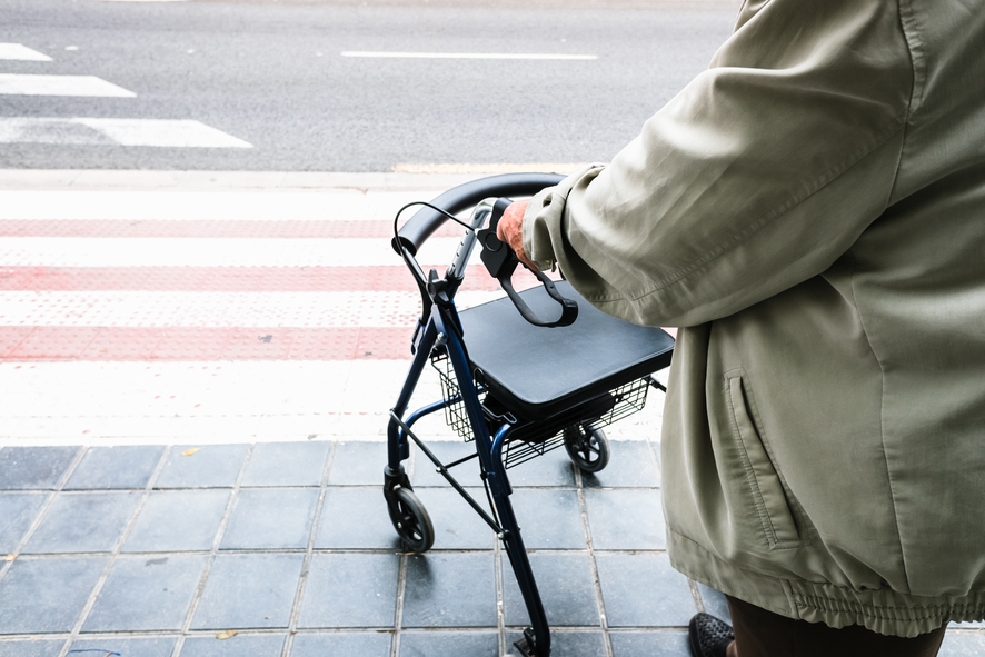 Elder waiting to cross a zebra crossing supported by a walker.